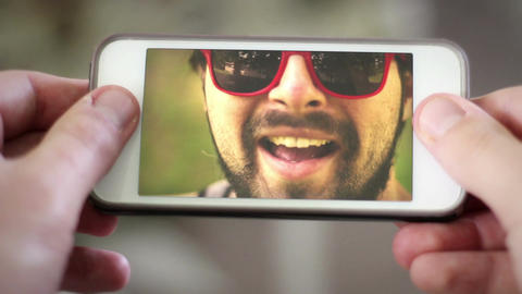 Video chatting with young urban hipster Millennial man over smartphone Footage