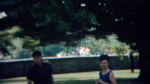 1968: Colorful retro style tour bus passes city park patrons Footage