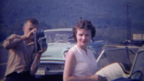 1966: Photographer loads camera while pretty retro women smiles Footage