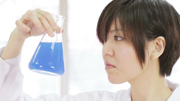 Female scientist inspects blue Erlenmeyer flask closeup Footage