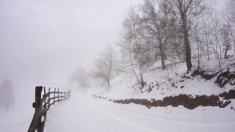 Fog rises on the mountainside covering hardwood roadside traversed in rapidly of Footage