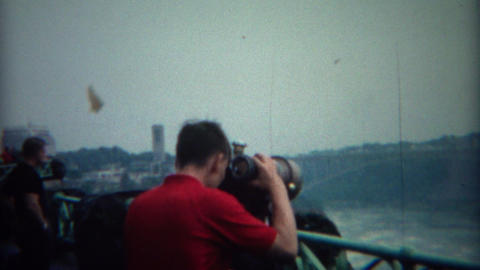 1969: Boy using binocular telescope at Niagara Falls to study waterfalls Footage