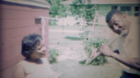 1967:African American man plays flute for wife outdoors Footage