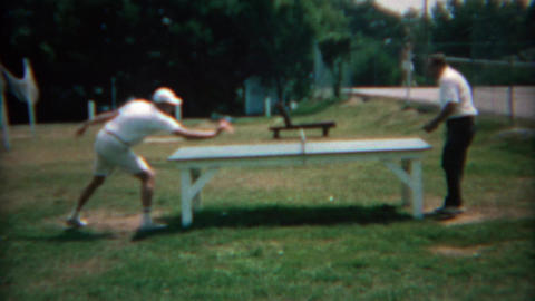 1969: Men play outdoor summer table tennis in the public city park Live Action