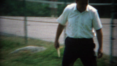 1969: Closeups of men play outdoor summer table tennis in the public city park Live Action