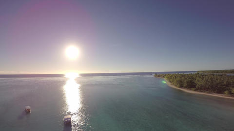 Aerial view over a tropical lagoon with boats in clear blue water during sunrise Live Action