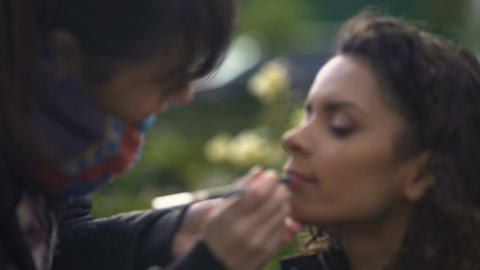 Make-up artist applying lipstick on models lips, natural beauty of young lady Footage