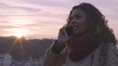 Cheerful young lady smiling and laughing during phone conversation, city sunset Footage