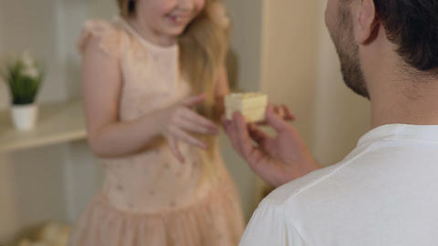 Excited little daughter surprised by fathers birthday present, happy family Footage