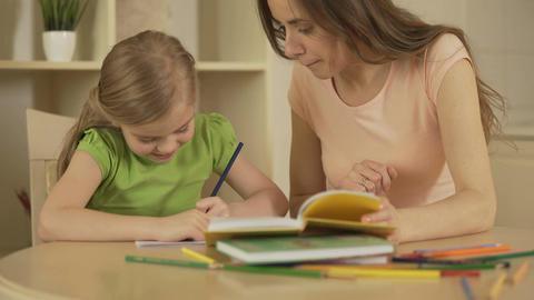 Mother helping daughter with homework, happy smart girl enjoying home education Footage