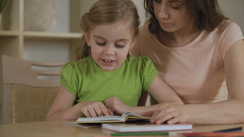 Girl reading interesting storybook for mother, woman proud of smart daughter Footage