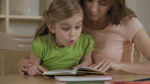 Supportive mother reading textbook together with hyperactive little daughter Footage