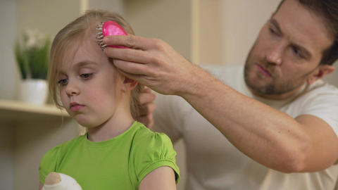 Strict father combing sad little daughter's hair with serious face, home tyrant Live Action