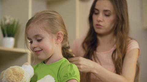 Smiling mother braiding happy little daughters hair, kissing her child with love Footage