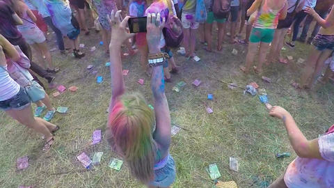 Cheerful young woman filming color festival atmosphere on gadget, top view Live Action