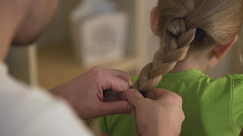 Father braiding daughter's hair carefully, taking care of beloved kid, family Footage