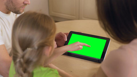 Happy family using application on tablet pc with pre-keyed green touchscreen Footage