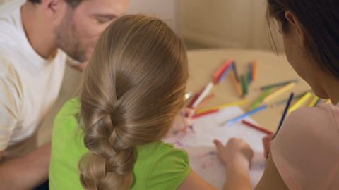 Family drawing colorful pictures with pencils, parents enjoying time with kid Footage