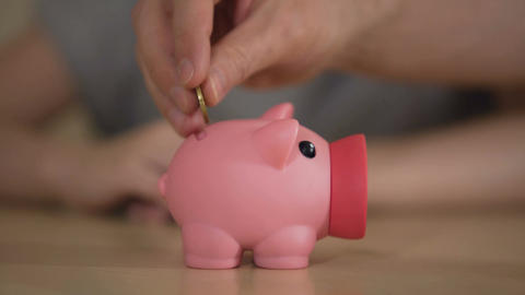 Parents and kid putting money in piggy bank for purchase, saving family budget Footage