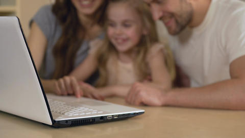 Happy parents and daughter looking at laptop, girl enjoying distance education Footage