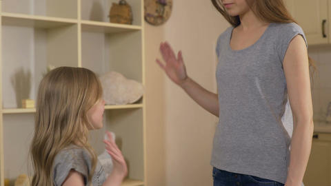Girl giving high five to big sister or mother, friendship and support in family Live Action