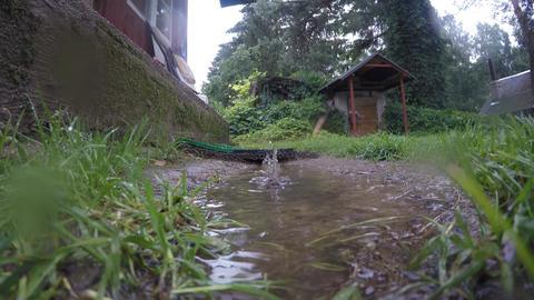 Rain drops fall and splash in water pool near rural wooden buildings. 4K Footage