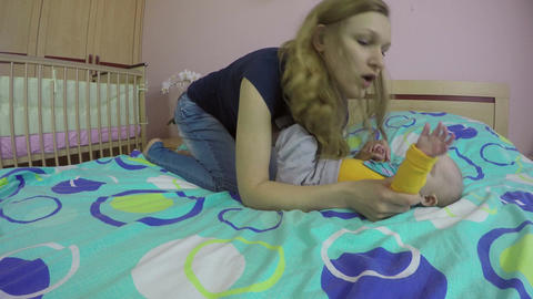 mom play with four month baby on bed home. Happy parental. 4K Footage