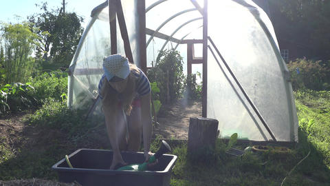 Hot farmer woman draw water with watering can from basin and water plants in hot Footage