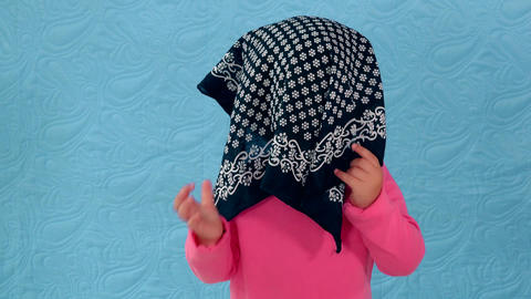 cute child play hide and seek with head scarf Footage