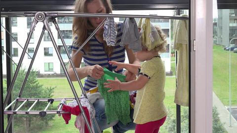 Little girl helping her mother woman to hang washed laundry Footage