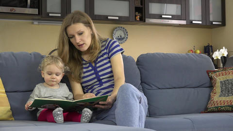 Woman and toddler child reading book together at home Live Action