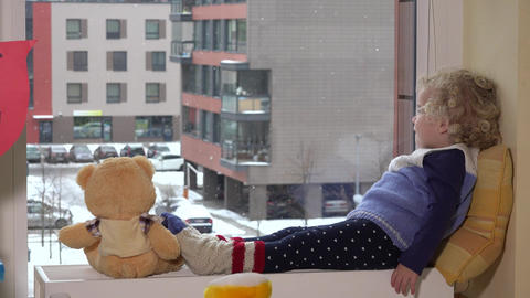 Toddler girl child talk with teddy bear excited to see snow outside Footage