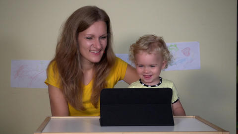 Young woman with her child girl looking funny cartoons on tablet computer Footage
