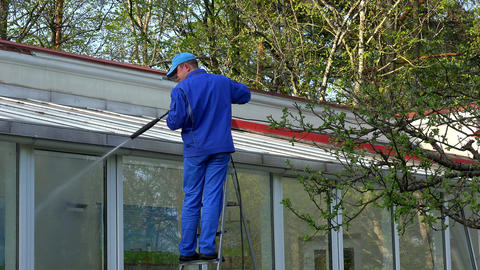 Man power washing conservatory roof and windows Footage