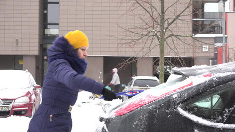 woman clean snowy car with brush in cold winter time. 4K Footage