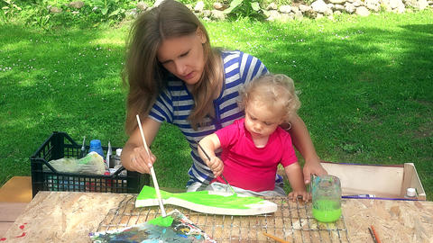 mother with her toddler daughter girl paint wooden fish decoration Footage