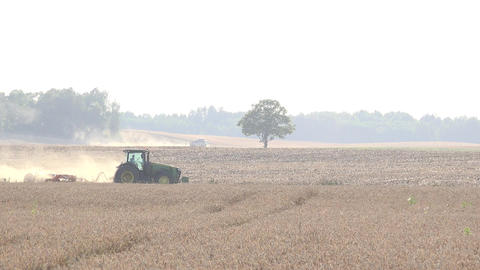 farmer with tractor prepare arable field soil with harrow tool for sowing in aut Footage