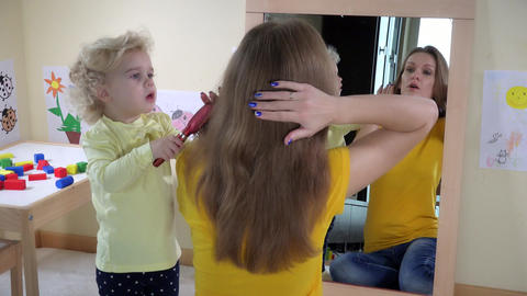 girl combing woman hair in front of mirror Footage