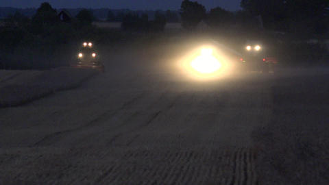 agricultural harvesting machines with lights working in wheat field at night dur Footage