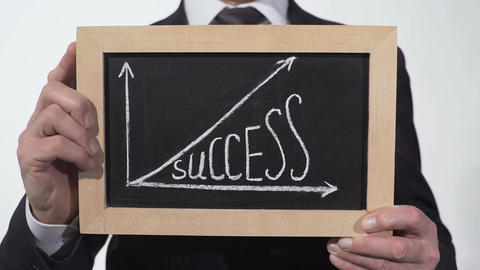 Success up arrow graphic drawn on blackboard in businessman hands, motivation Footage