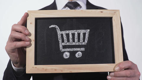 Shopping cart on blackboard in businessman hands, retail trade, consumer bundle Footage