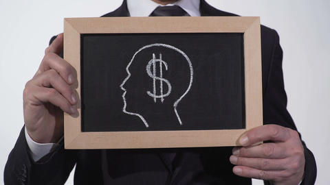 Dollar symbol head image on blackboard in businessman hands, greed for money Footage