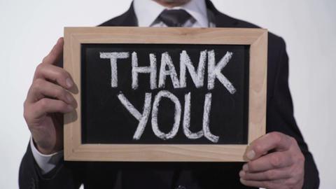 Thank you written on blackboard in businessman hands, donation appreciation Footage