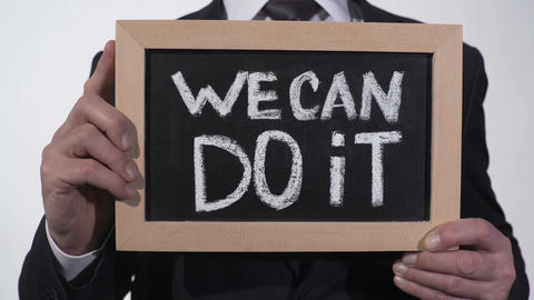 We can do it motivation phrase on blackboard in businessman hands, support Footage