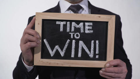 Time to win motivation phrase on blackboard in businessman hands, inspiration Footage