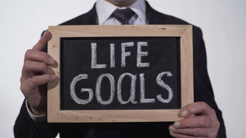 Life goals written on blackboard in businessman hands, success tips, motivation Footage
