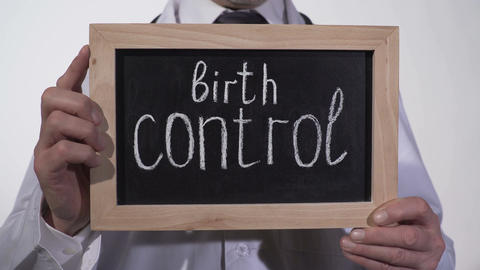Birth control written on blackboard in therapist hands, pregnancy prevention Live Action