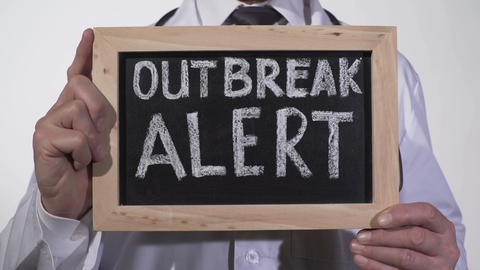 Outbreak alert text written on blackboard in doctor hands, epidemic warning Footage