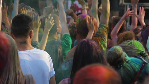 Joyful people waving hands and dancing at Holi fest, vacation, open-air party Footage