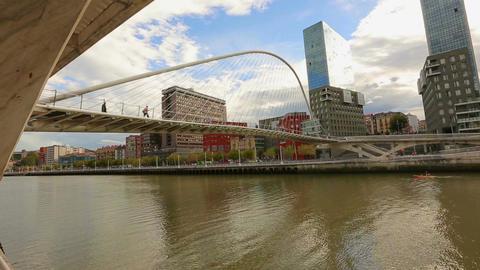 People walking across contemporary Zubizuri glass bridge in Bilbao, Spain Footage